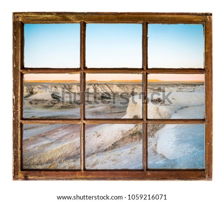 badlands and grassland at dusk as seen through vintage, grunge, sash window with dirty glass