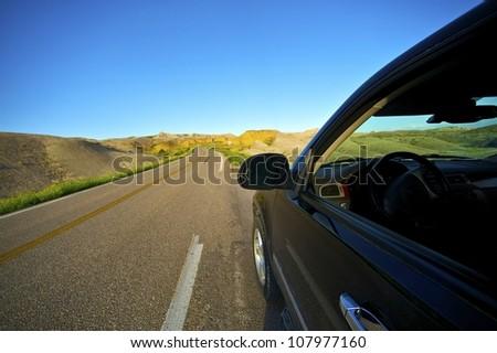 Badlands Drive Thru. Traveling Theme with Black SUV on the Loop Road in Badlands National Park, South Dakota, USA. #107977160