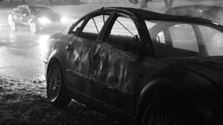 Badly damaged car at the scene of a collision in winter conditions at night. Black and white. High quality photo