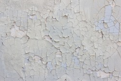 Badly fixed building facade wall covered with cracks in stucco and light gray painting.