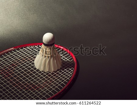 Badminton and racket on black background.