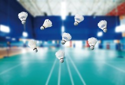 badminton - badminton courts with players competing; shuttlecocks in the foreground