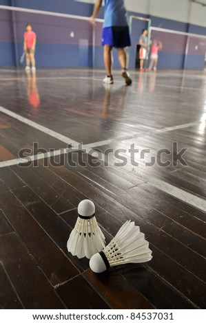 Badminton - two shuttlecocks in the badminton courts with player