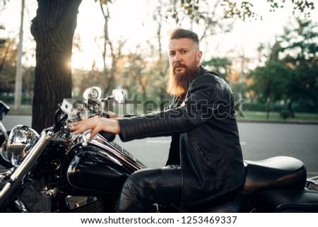 Baerded biker poses on chopper leaning on a helmet #1253469337