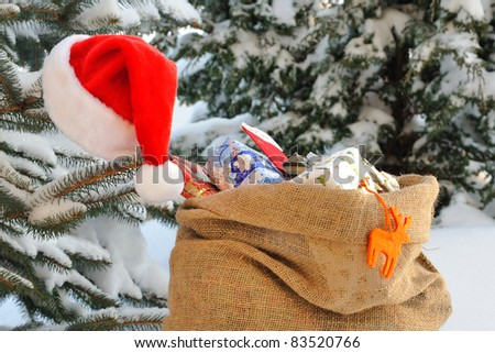 Bag of Christmas presents in the snow. - stock photo