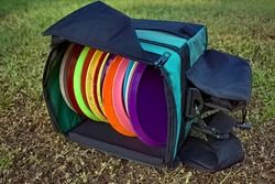 Bag of disc golf discs laying on grass.