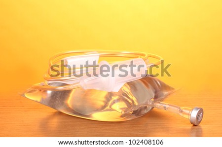 Bag of intravenous antibiotics and plastic infusion set on wooden table on yellow background