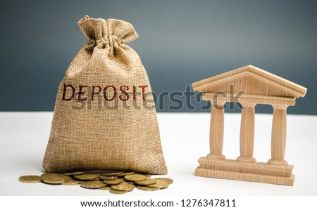 Bag of money with the word Deposit near the bank. The amount of money transferred by a person to a credit institution in order to receive income in the form of interest. Investment in bank