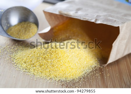 Bag of polenta spilling onto a cutting board with tablespoon in the background