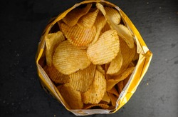 Bag of potato chips or crisps isolated on a black stone background. Close-up of potato chips or crisps. Food background.