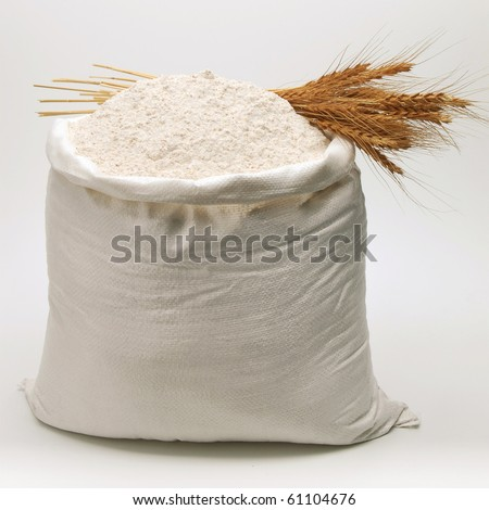 Bag of whole flour with bunch of wheat on white background