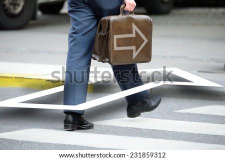 Bag with arrow. Suit (man) crossing street
