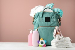Bag with diapers and baby accessories on white wooden table against pink background. Space for text