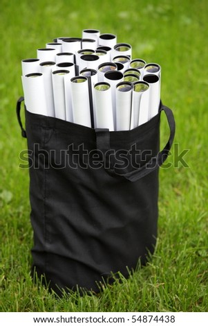 Bag with ecological posters on the grass background