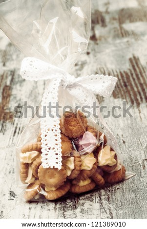 Bag with iced gem biscuits on wooden table
