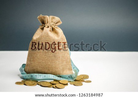 Bag with money and tape measure and the word budget. Limited budget. Lack of money. The concept of accumulating money in the family budget. Family Insurance. Distribution of cash savings. Saving money