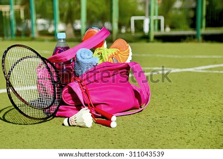Bag with sports equipment on the sports courts background. Badminton ball (shuttlecock), racket, rope, sneakers, bottle of water, towel are in the bag in the sunny day. Healthy lifestyle. Copy space.