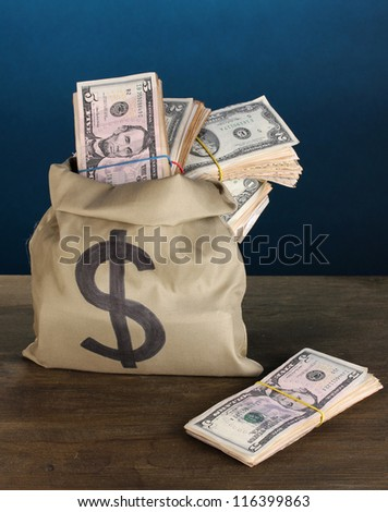 Bag with stacks of dollars on wooden table on blue background