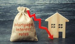 Bag with the money and the word Mortgage interest rates and arrow to down and house. Low interest in mortgages. Reducing interest payments for mortgages. The fall in housing rates on credit. Low