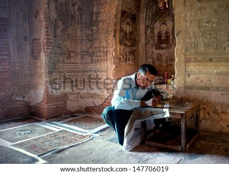 BAGAN, MYANMAR - FEBR. 4:Unidentified  man is painting replica artwork inside the Gawdawpalin Temple on februari 4 2013 Myanmar.There are over 300 monuments in Bagan which has mural paintings inside.