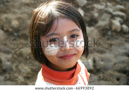 BAGAN, MYANMAR-JAN 4:  Unidentified girl demonstrates the use of Thanaka, a yellowish-white paste made from ground bark & used as a cosmetic and for sunburn protection on Jan 4, 2010 in Bagan Myanmar.
