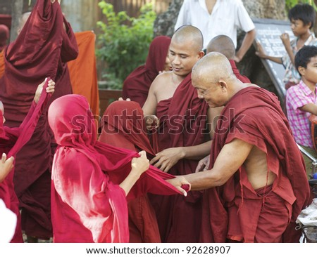 BAGAN, MYANMAR: OCT 14: Two adult monks helping novice monks to put on their traditional red robes in Bagan, Myanmar on October 14, 2011. Eighty nine percent of the Burmese population is Buddhist.
