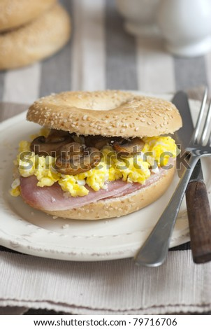 Bagel filled with scrambled egg, mushrooms and bacon