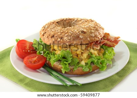 Bagel with salad, scrambled eggs and crispy bacon