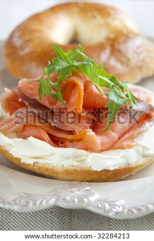Bagel with smoked salmon and cream cheese, topped with rocket (arugula).  Shallow DOF.