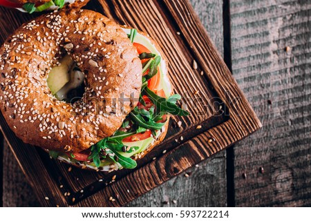 Shutterstock Bagels with cream, avocado, tomatos and arugula on wooden board and table background. Healthy breakfast food. Top view and Copy space