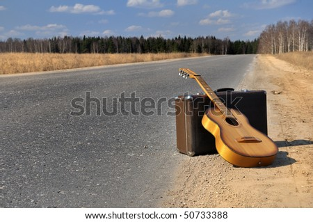 baggage and guitar lies on empty countryside road