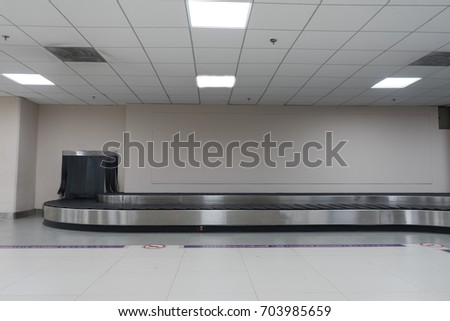 Baggage conveyor belt in arrivals lounge of airport terminal