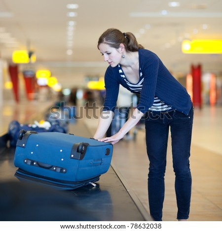 Baggage reclaim at the airport - pretty young woman taking her suitcase off the baggage carousel - stock photo