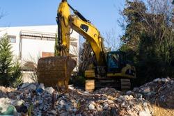 Bagger, excavator digging through debris, demolished old building