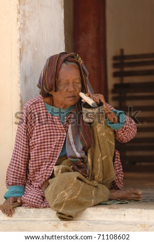BAGO, MYANMAR - DECEMBER 25: Old woman sits in front of the Buddhist temple on December 25, 2007 in Bago during local religion festival, Myanmar. Woman smokes pretty long and thick cigar.
