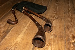 Bagpipe is a traditional musical instrument lying on a wooden floor.