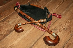 Bagpipe is a traditional musical instrument on a wooden background. Close-up.
