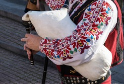 Bagpiper in traditional Bulgarian national costume plays folk musical wind instrument - bagpipes at festival on street in city of Plovdiv, Bulgaria. Bulgarian folklore and culture