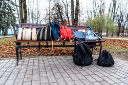 bags and backpacks lie on a Park bench.