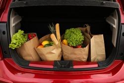 Bags full of groceries in car trunk, closeup view