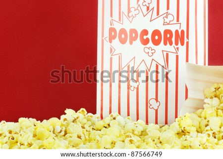 Bags of buttery popcorn against a red background with copy space.