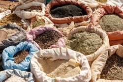bags of colored spices and other herbs in the ethiopian market standing in the hot sun