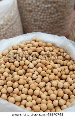 Bags of dry Soya beans from the market as a textured food background. Shallow DOF, focus on lower third.