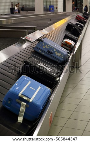 Bags & suitcases on a luggage conveyor belt in the baggage claim at an airport #505844347