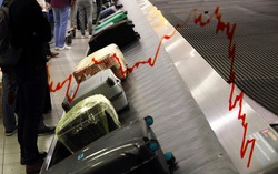 Bags & suitcases on a luggage conveyor belt in the baggage claim at an airport and negative stock market trendline