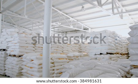 Bags with flour in warehouse of flour factory. Flour stock. Mill warehouse.