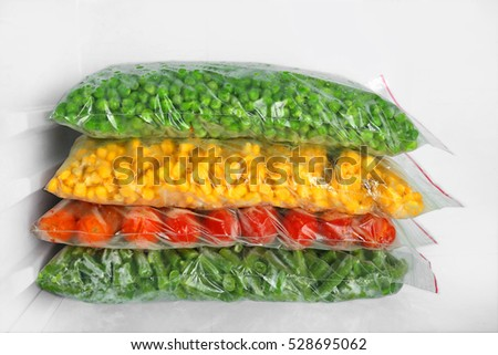 Bags with frozen vegetables in refrigerator, closeup