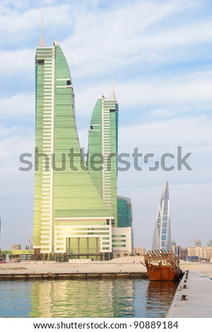 Bahrain Manama city view with Financial center and a dhow boat on foreground in a cloudy day - stock photo