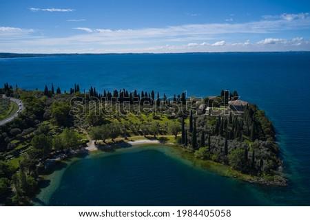 Baia delle Sirene on the coastline. Aerial view of Parco Baia delle Sirene, Lake Garda, Italy. Top view of baia delle sirene on the coastline of Lake Garda. Panorama of punta san vigilio. Foto d'archivio ©