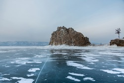 Baikal frozen lake, Olkhon island - Shaman rock, Burkhan cape. Clear ice and snow. Traveling in winter. Baikal - the deepest lake on the planet